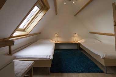 op de eerste verdieping bevinden zich twee slaapkamers de eerste slaapkamer heeft twee eenpersoons bedden en een wastafel